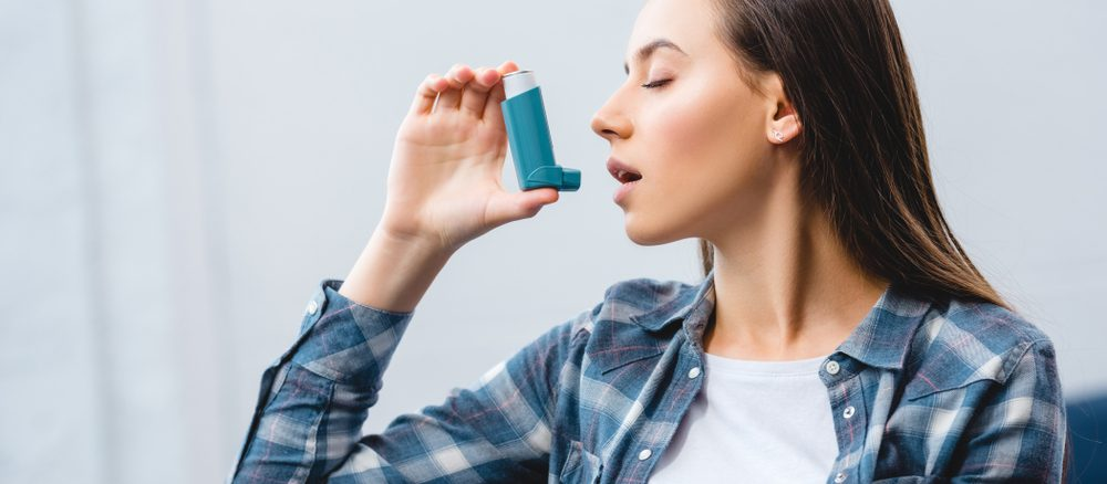 A girl using inhaler while suffering from Asthma-COPD overlap syndrome at home.
