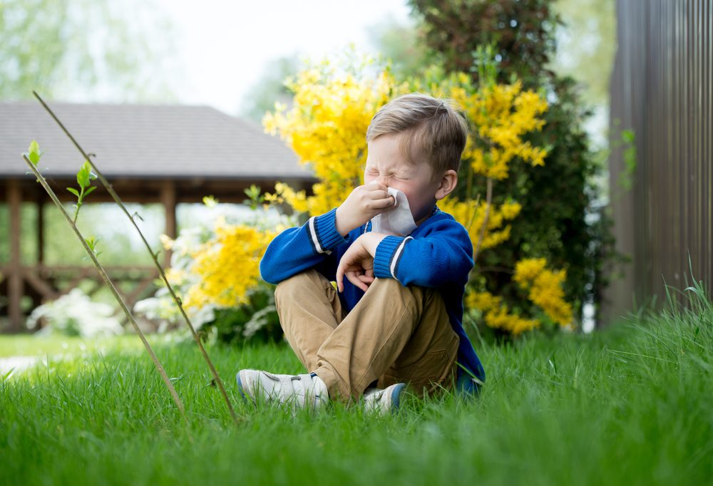 A child is sitting on the grass and sneezing due to a Grass allergy.