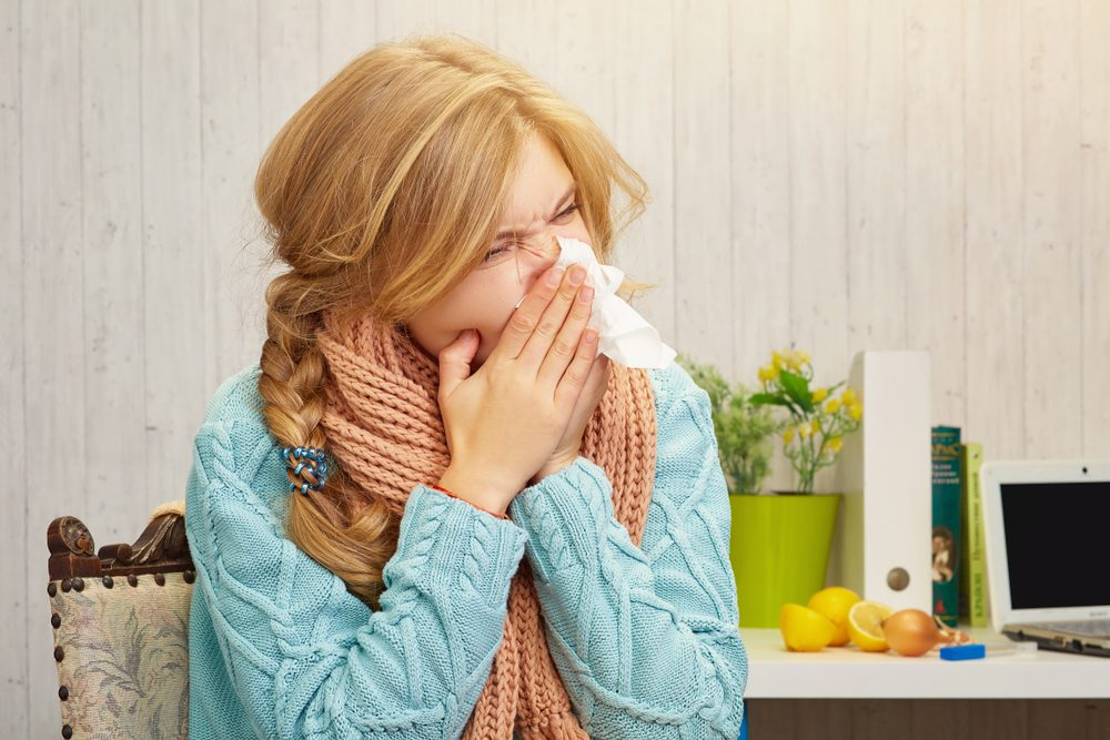 A girl blows her nose in a handkerchief due to the onion allergy against the background on which lies an onion and lemon with laptop and books.