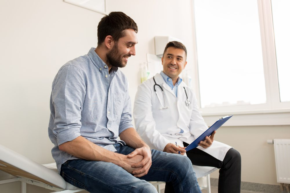 Smiling doctor with clipboard and young man patient meeting at Allergy Partners of Fredericksburg.